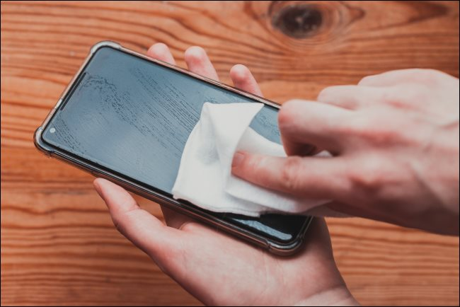 A person cleaning a phone with a disinfecting wipe.